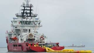 Red and white ship towing a yellow inflatable boom