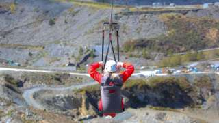 A woman hanging from a zip wire