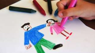 Child drawing an image of domestic abuse