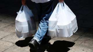 Takeaway food in containers being carried in white plastic carrier bags