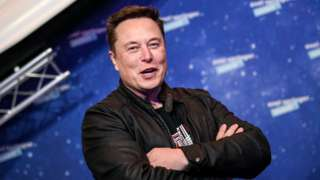 Elon Musk laughs with arms folded in this file photo