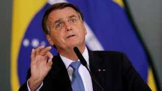 Bolsonaro discursa no microfone, com bandeira do Brasil atrás