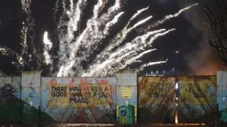 A firework exploding over a peace wall in west Belfast