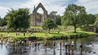 Bolton Priory overlooks the River Wharfe as families cross on stepping stones