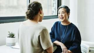 Dos mujeres hablando en un despacho