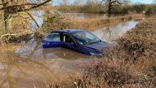 Car stuck in flooded lane