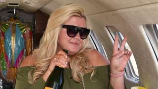 Gemma Collins holds a bottle of champagne in a private jet