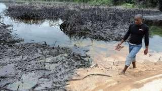 Man dey waka pass oil spill