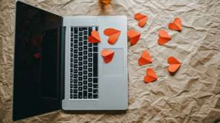 Laptop with red paper hearts scattered around it