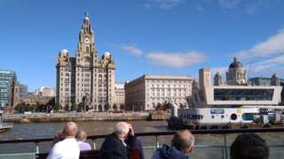passengers on Mersey Ferry look at liver buildings