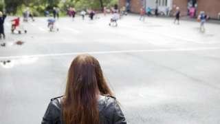 Garota sozinha em escola