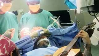 Musa Manzini plays his guitar on the operating table