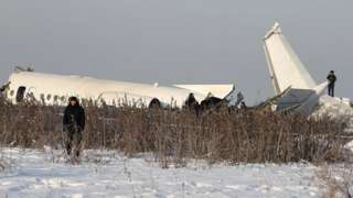 Emergency and security personnel are seen at the site of a plane crash near Almaty, Kazakhstan, December 27, 2019