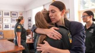La primera ministra de Nueva Zelanda, Jacinda Ardern, abraza a mujer miembro del equipo de emergencias.