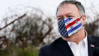Mike Pompeo wearing a face mask with a US flag on it, standing in the occupied Golan Heights