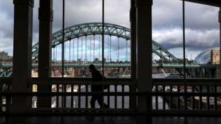 A pedestrian crosses the High Level Bridge between Gateshead and Newcastle, with the Tyne Bridge in the background