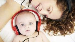 Bebê com fones de ouvido ao lado de sua mãe