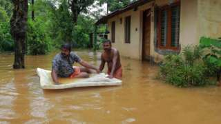 Men pass through flood waters in the southern Indian state of Kerala