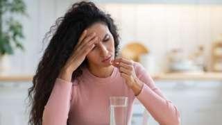 Una mujer con resaca toma una pastilla