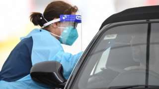 A healthcare worker wearing full protective clothing tests a driver for Covid-19 at a drive-in clinic in Sydney