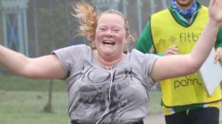 Dawn Nisbet crossing the finish line with her hands in the air and a big smile on her face
