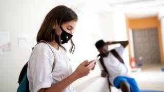 Em corredor de escola, menina mexe em celular, e menino aparece sentado atrás, ambos de uniforme