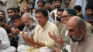 Pakistani cricketer-turned-politician and head of the Pakistan Tehreek-i-Insaf (PTI) Imran Khan (L) prays with elder brother Aslam Raisani of Siraj Raisani, a candidate of provincial seat who was killed on July 13 suicide bombing in Mastung during an election campaign