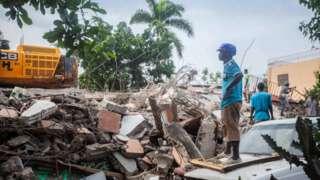 A worker surveys rubble