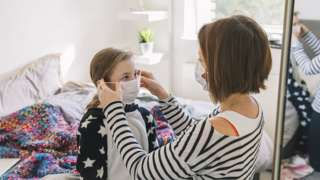 Woman putting mask on girl
