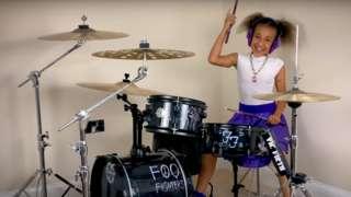 Nandi Bushell sat at drum kit ready to play