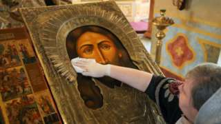 A believer sanitises an icon case in the Church of St Alexius, Moscow, March 2020