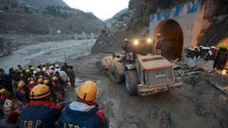 Members of Indo-Tibetan Border Police (ITBP) watch as a machine is used to clear a tunnel after a part of a glacier broke away, in Tapovan in the northern state of Uttarakhand, India, February 8, 2021