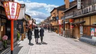 Tres personas en una calle limpia de Japón