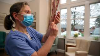 A doctor prepares to give a dose of the vaccine at a nursing home in Shropshire