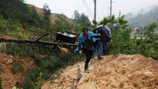 Men cross a mudslide blocking a road after the passage of Storm Eta, in Purulha, Baja Verapa