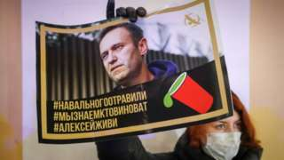 """Protester holds poster with hashtags """"Navalny was poisoned"""", """"We know who's to blame"""" and """"Alexei, stay alive"""""""