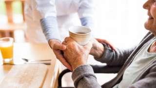 Carer giving drink to elderly patient