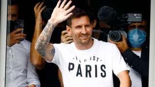 Lionel Messi waving to fans wearing a Paris t-shirt