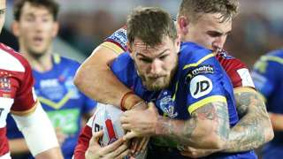 Daryl Clark of Warrington Wolves is caught by Sam Powell of Wigan Warriors