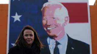 Laurita Blewitt pictured in front of a Joe Biden mural in Ballina