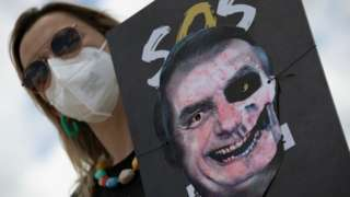 Mulher de máscara segura cartaz em que foto de Bolsonaro foi transformada em figura assustadora