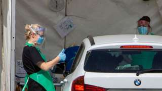 woman in visor and surgical gloves giving thumbs up to person in car