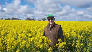 Victorian grain grower Chris Kelly standing in a field of canola in his farm in the southern Mallee region