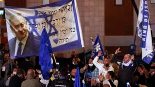 Supporters of Israeli Prime Minister Benjamin Netanyahu's Likud party react following the release of exit polls for the general election on 23 March 2021