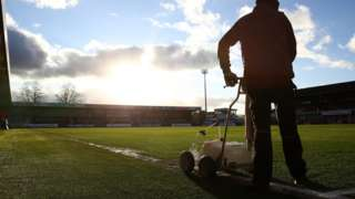 Ground staff paint the lines at Cheltenham Town