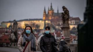 Women, wearing face masks, walk on the Charles Bridge in Prague, Czech Republic