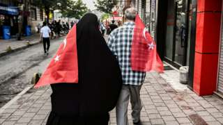 Two people walking carrying Turkish flags