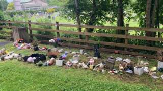 Trinkets strewn across the grass in the memorial garden