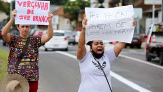 """Two protesters carry signs """"Ashamed of being white"""" and """"Please stop killing us"""" outside a Carrefour supermarket in Porto Alegre, Brazil, on 20 November 2020"""