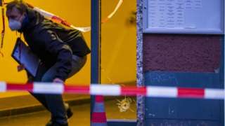 A policeman walks past a hole from a bullet in a window at a crime scene in Berlin's Kreuzberg district on December 26, 2020, following a shooting.